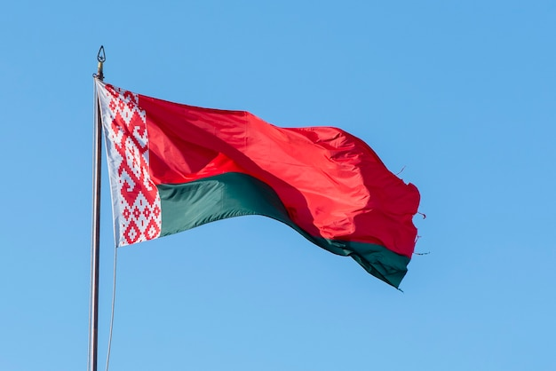 Bandiera della bielorussia sventola contro il cielo blu