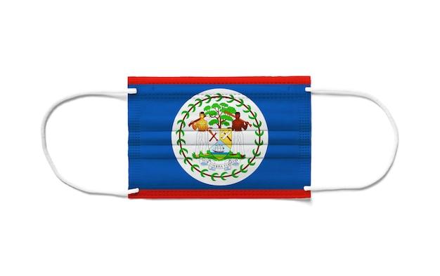 Bandiera del belize su una maschera chirurgica monouso. superficie bianca isolata