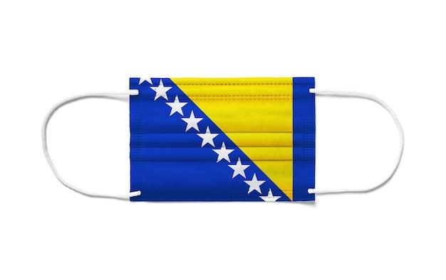 Bandiera della bosnia ed erzegovina su una maschera chirurgica monouso. superficie bianca isolata