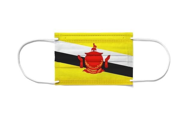 Bandiera del brunei su una maschera chirurgica monouso. superficie bianca isolata