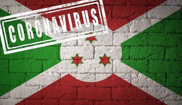 Bandiera del burundi sulla trama del muro di mattoni stampata del concetto di virus corona coronavirus