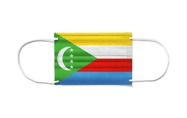 Bandiera delle comore su una maschera chirurgica monouso. superficie bianca isolata