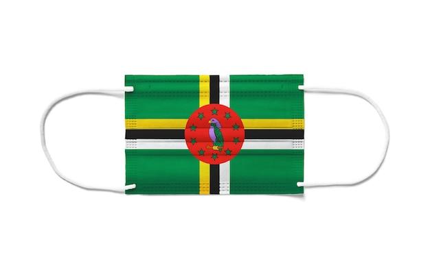 Bandiera della dominica su una maschera chirurgica monouso. superficie bianca isolata
