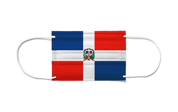 Bandiera della repubblica dominicana su una maschera chirurgica monouso. superficie bianca isolata