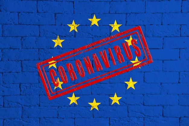 Bandiera dell'ue o dell'unione europea sulla trama del muro di mattoni. timbrato di coronavirus. concetto di virus corona. sull'orlo di una pandemia di covid-19 o 2019-ncov. nuovo focolaio cinese di coronavirus