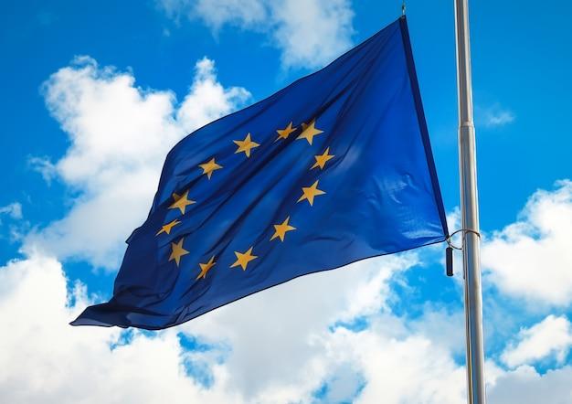 Bandiera dell'unione europea contro un cielo nuvoloso blu. il simbolo ufficiale dell'ue.
