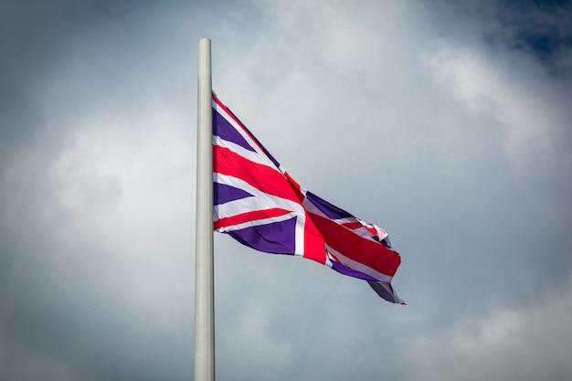 Bandiera della gran bretagna che fluttua nel vento contro un cielo nuvoloso