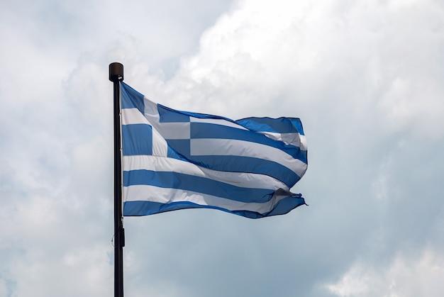 Bandiera della grecia sul pennone contro le nuvole