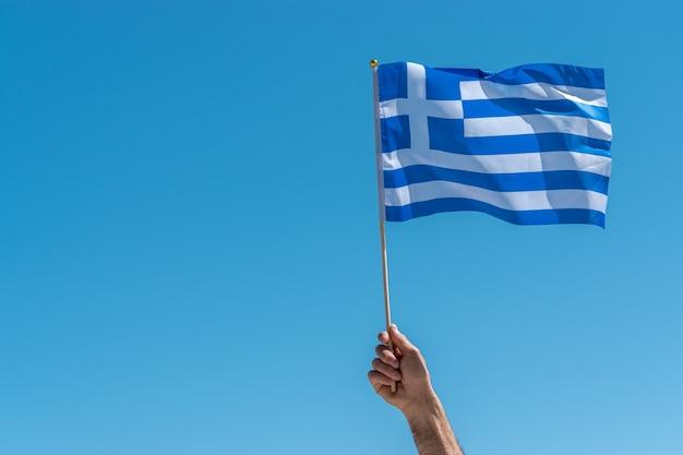 Bandiera della grecia in mano umana sullo sfondo del cielo