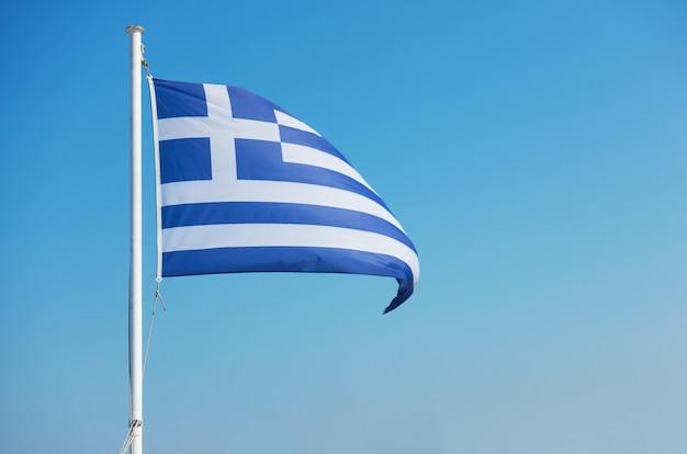Bandiera della grecia - sventolando la bandiera greca contro il cielo blu. spazio per il tuo testo