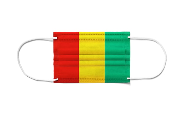 Bandiera della guinea su una maschera chirurgica monouso. superficie bianca isolata