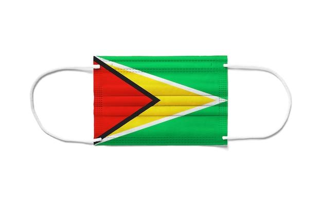 Bandiera della guyana su una maschera chirurgica monouso. superficie bianca isolata