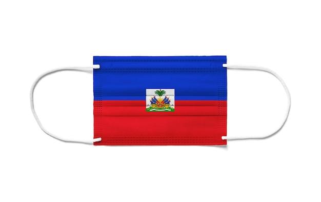 Bandiera di haiti su una maschera chirurgica monouso. superficie bianca isolata
