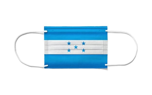 Bandiera dell'honduras su una maschera chirurgica monouso. superficie bianca isolata