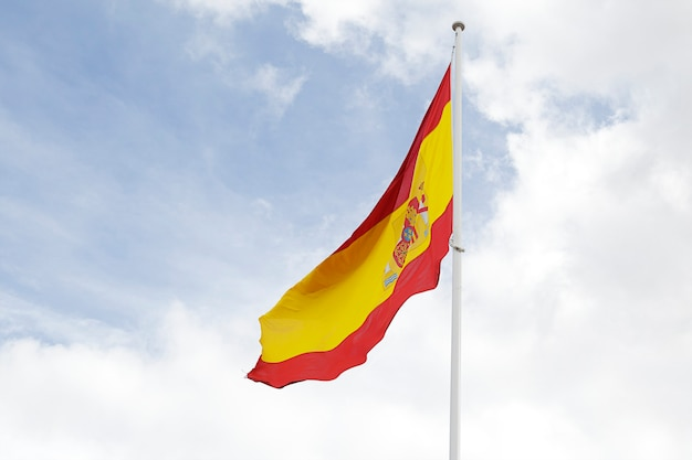 Bandiera della spagna contro il cielo blu nuvoloso