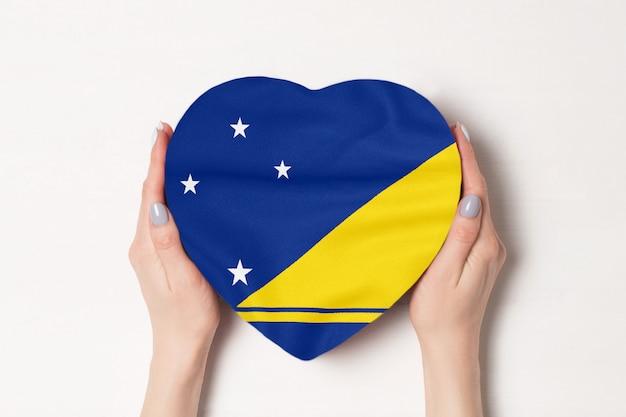 Bandiera di tokelau su una scatola a forma di cuore in mani femminili