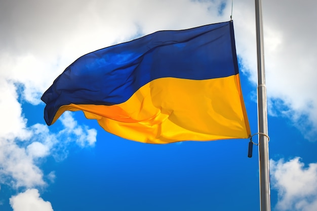 Bandiera dell'ucraina contro un cielo nuvoloso blu.