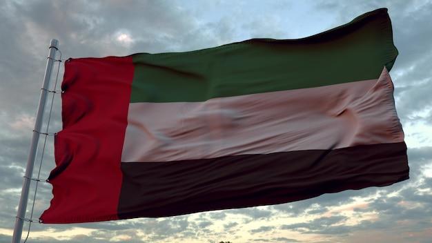 Bandiera degli emirati arabi uniti che fluttua nel vento contro il bel cielo profondo al tramonto