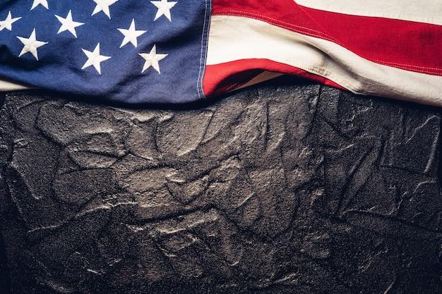 Bandiera degli stati uniti su sfondo nero o scuro con texture.