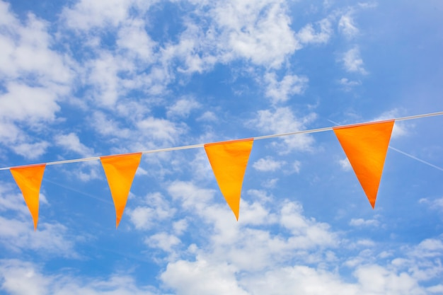 Bandiere in colore nazionale olandese arancione nel cielo azzurro con la luce del sole per celebrare il giorno dei re