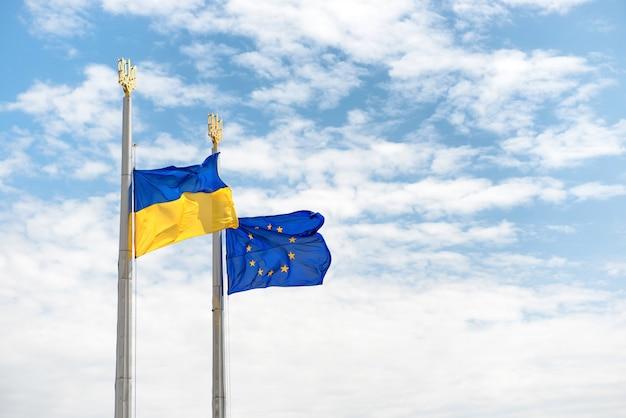 Bandiere dell'europa e dell'ucraina sui pali con cielo blu come sfondo