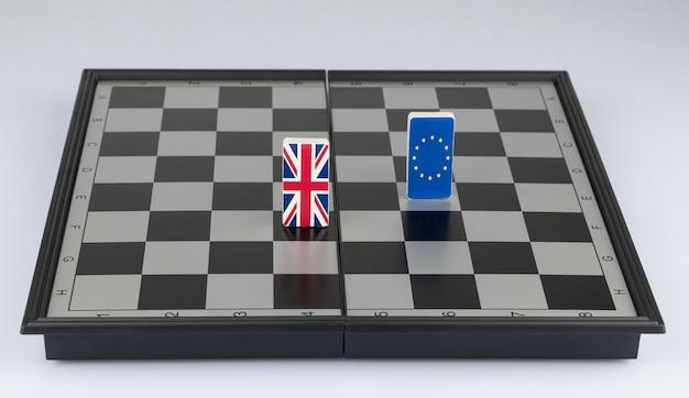 Bandiere dell'unione europea e della gran bretagna sulla scacchiera il concetto di gioco politico e strategia