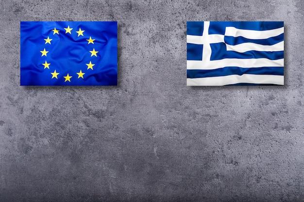 Bandiere dell'unione europea e della grecia su sfondo concreto.