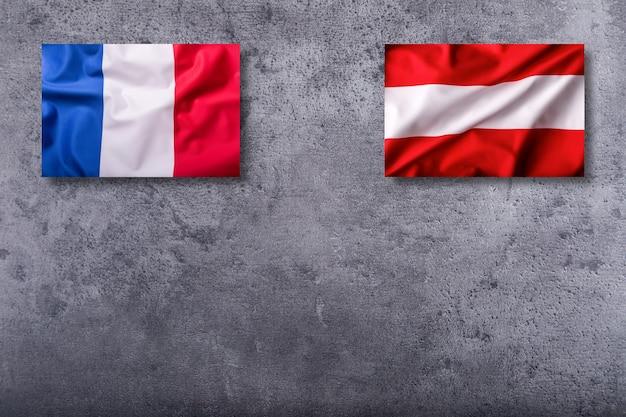 Bandiere della francia e dell'austria su fondo concreto.