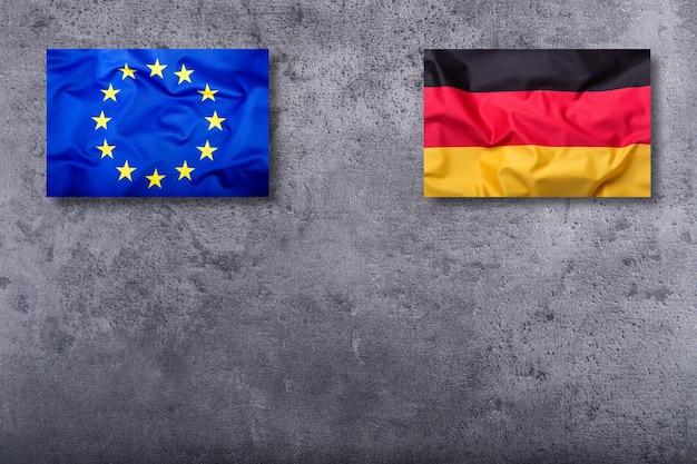 Bandiere della germania e dell'unione europea su sfondo concreto. Foto Premium
