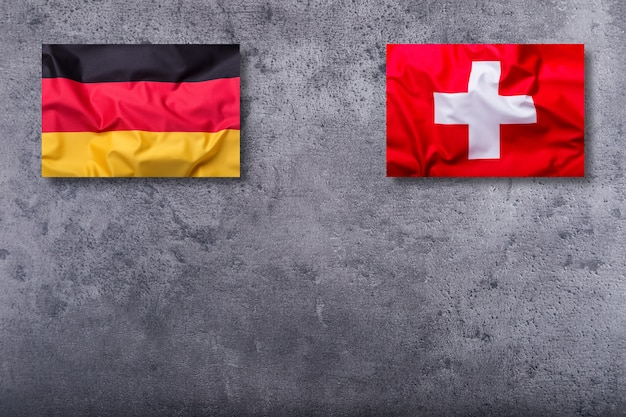 Bandiere della germania e della svizzera su sfondo concreto.