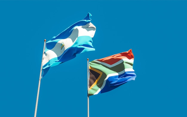 Bandiere del nicaragua e del ras africano sul cielo blu. grafica 3d