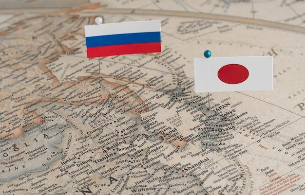 Le bandiere della russia e del giappone sulla mappa del mondo differenze politiche dovute all'isola di sakhalin