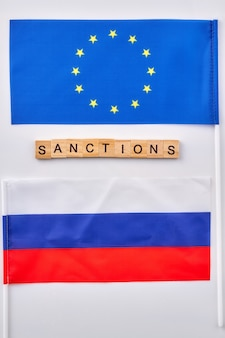 Bandiere della russia e dell'unione europea. sanzioni verbali fatte di cubi di legno.