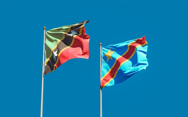 Bandiere di saint kitts e nevis e repubblica democratica del congo sul cielo blu. grafica 3d