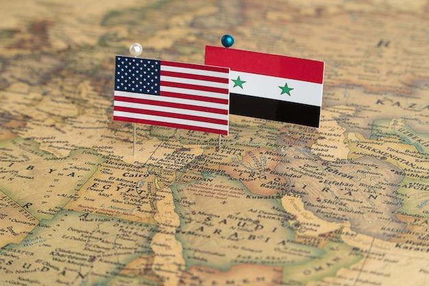 Bandiere degli stati uniti e della siria sulla mappa del mondo politica e conflitto militare di ordine mondiale