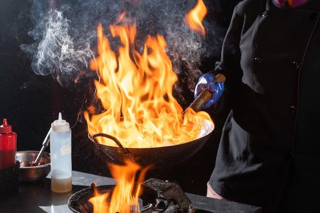 Flambe padella wok, cottura sul fuoco. cucina panasiatica. cibo di strada.