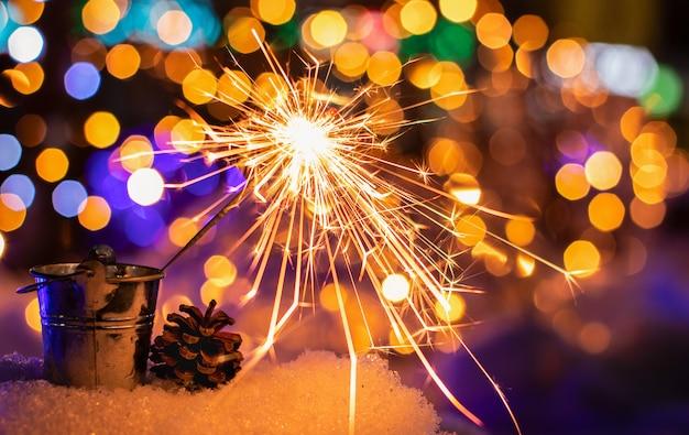Fiamme del fuoco del bengala nella città di notte con le luci del bokeh