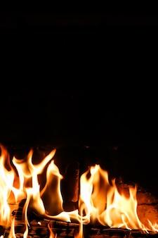 Fiamme di fuoco su sfondo nero il mistero dello spazio del fuoco per copiare il testo le tue parole in verticale
