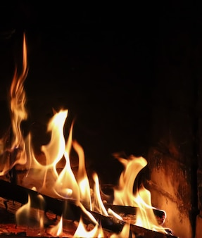 Fiamme di fuoco su uno sfondo nero il mistero dello spazio del fuoco per copiare il testo le tue parole in verticale