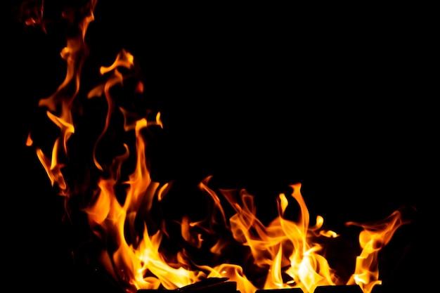 Fiamme di fuoco dai carboni ardenti nella griglia a tarda notte.