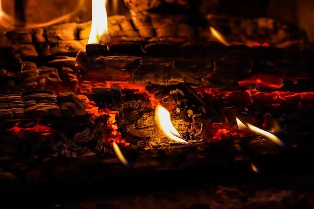 Fiamme di fuoco e carboni ardenti di legna bruciata nel camino