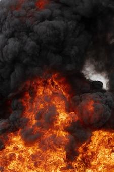 Fiamme di forte fuoco rosso e sfocatura di movimento nuvole nere fumano cielo coperto. movimento sfocato da un enorme fuoco arancione e alta temperatura pericolosa dalle fiamme. messa a fuoco selettiva morbida.
