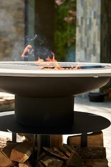 Carbone ardente nel pozzo della griglia del bollitore con la griglia del ghisa piano cottura da tavolo rotondo. griglia calda per barbecue con griglia in acciaio inossidabile sul cibo da cuocere alla griglia pronto per il cortile. griglia con fiamme all'interno.