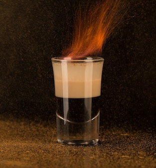 Cocktail fiammeggiante con cannella in un bicchierino su sfondo nero, isolato