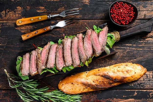 Panino baguette di bistecca di fianco con rucola su un tagliere. fondo in legno scuro. vista dall'alto.