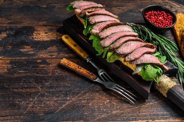 Panino baguette di bistecca di fianco con rucola su un tagliere