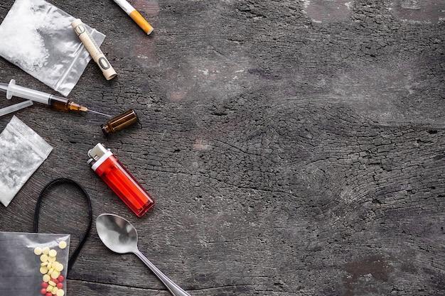 Ketamina piatta e siringa, elastico, vecchio cucchiaio, accendisigari, anfetamine, pillole di ecstasy su sfondo di legno con spazio di copia. droga pericolosa. sostanza che crea dipendenza. concetto di narcotico.