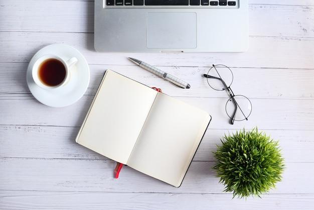 Caffè, blocco note e computer portatile piani della composizione su fondo bianco.
