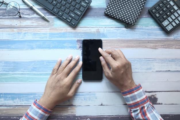 Composizione piatta della mano utilizzando smart phone su sfondo di legno.