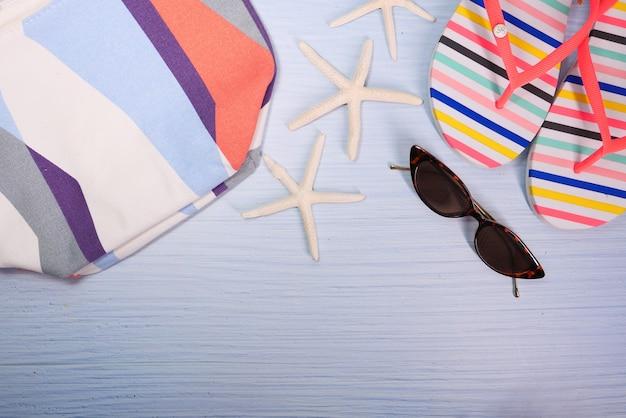 Composizione piatta di accessori da spiaggia estivi sul tavolo.